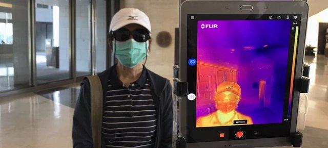 Un termómetro de infrarrojos se utiliza para comprobar la temperatura de los huéspedes en la entrada de un hotel en Yangon, Myanmar.