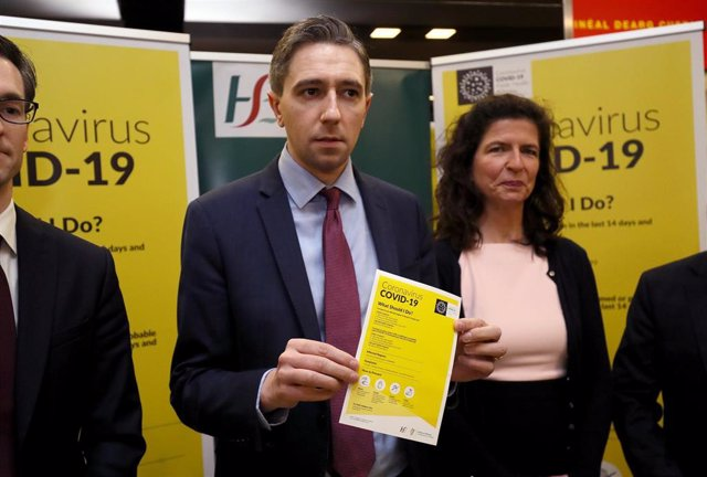 28 February 2020, Ireland, Dublin: UK Minister for Health Simon Harris (C) holds a leaflet which forms part of the public awareness campaign for COVID-19 (Coronavirus) at the baggage hall of Terminal 2 of the Dublin Airport. Photo: Brian Lawless/PA Wire/d