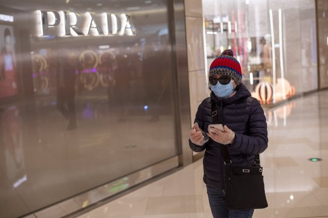 February 26, 2020 - Shanghai, China: A female shopper wears a surgical mask and sunglasses and plastic gloves outside the Prada store at the iapm luxury mall. (Dave Tacon/Contacto)