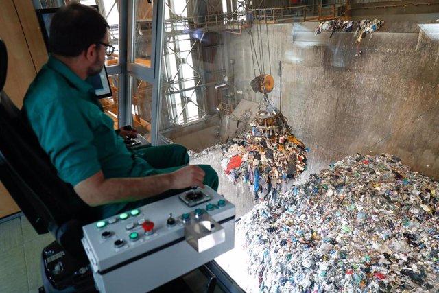 Un trabajador del Parque Tecnológico de Valdemingómez, mueve desde una grua una montaña de residuos.