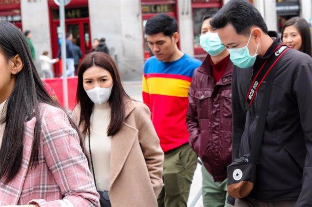Recursos de transeúntes por el centro de Madrid con mascarillas tras el anuncio de casos de coronavirus en España