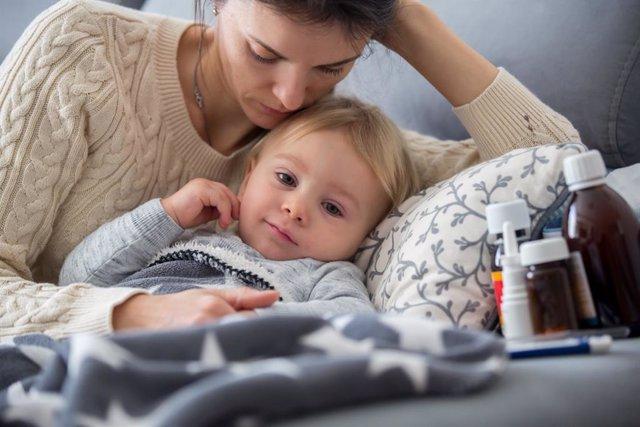Bebé enfermo en la cama cuidado por su madre.