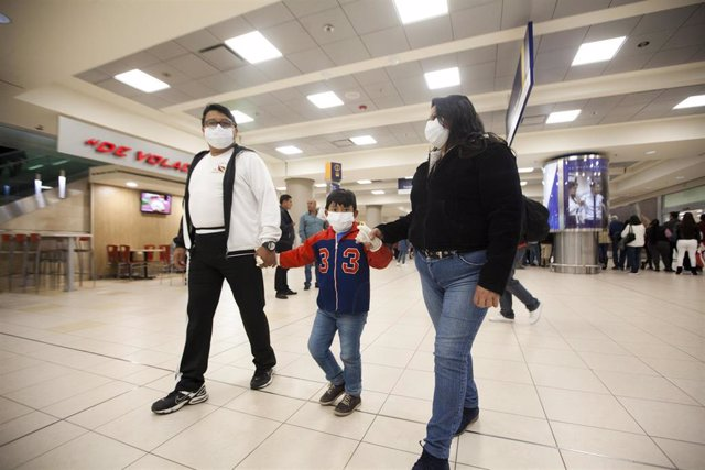 29 February 2020, Ecuador, Quito: Family members wear mouthguards at Mariscal Sucre International Airport. The first case of coronavirus was confirmed in the South American country on Saturday. Photo: Juan Diego Montenegro/dpa