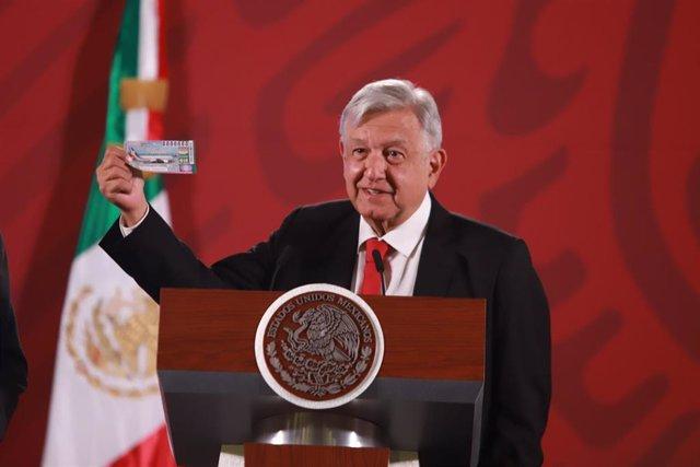 Andrés Manuel López Obrador sostiene un boleto del sorteo del avión presidencial