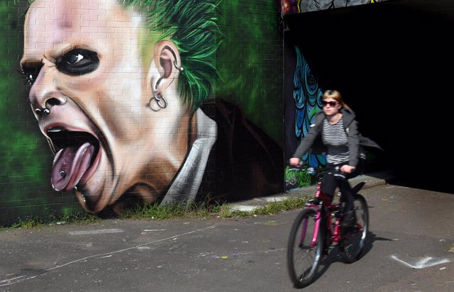 29 March 2019, England, Braintree: A woman cycles past a mural of Keith Flint, English musician and founder of the electronic music band 'Prodigy', ahead of his funeral. Photo: Joe Giddens/PA Wire/dpa