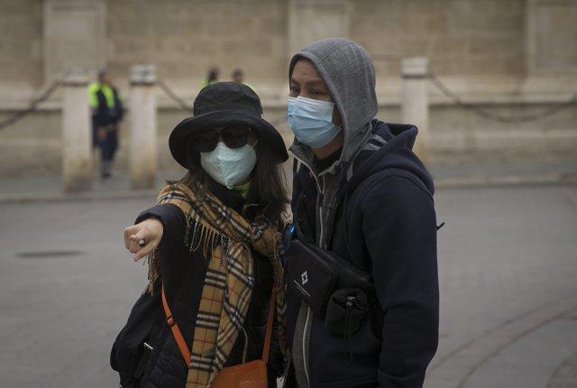 Dos turistas con mascarillas para evitar el contagio por coronavirus.
