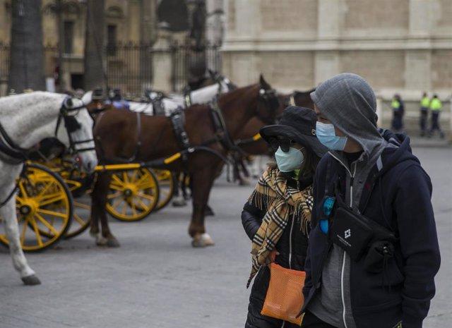 Imágenes del impacto del virus del Coronavirus en el sector turístico . Dos turistas con mascarillas pasean por el centro de Sevilla (Andalucía, España), a 03 de marzo de 2020.
