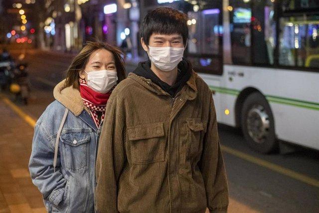 Peatones con mascarillas en Shanghái