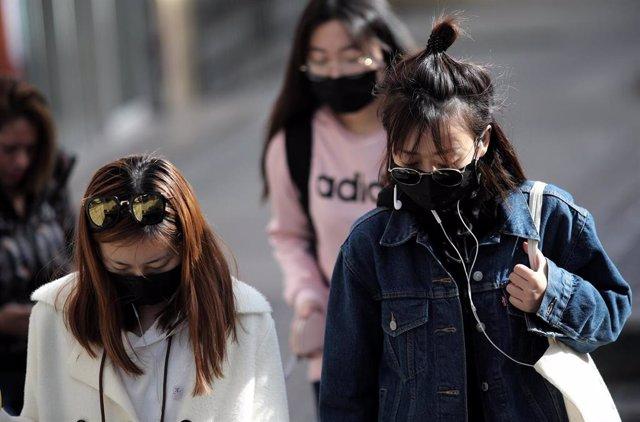 Tres jóvenes de rasgos asiáticos caminan por el distrito madrileño de Usera protegiendo su rostro con mascarillas
