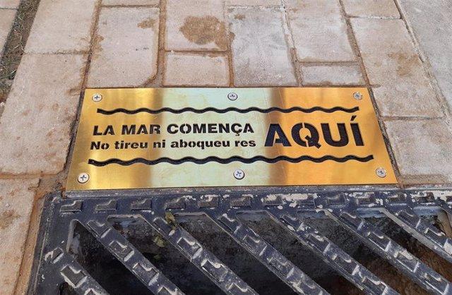 Placa con el mensaje 'El mar empieza aquí', una campaña de Emaya para evitar el lanzamiento de residuos a las alcantarillas.