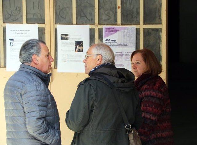 Pla mig de tres veïns de Castellterçol davant els cartells que anuncien algunes de les activitats que es faran. Imatge del 7 de març del 2020. (Horitzontal)