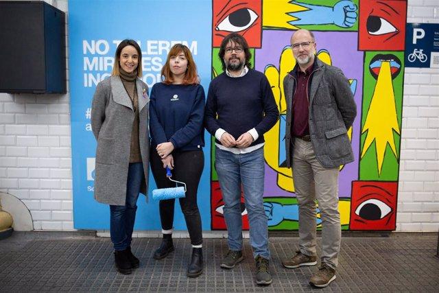 La presidenta de l'Institut Català dels Dons (ICD), Núria Ramon, la il·lustradora Cristina Daura, i el president de Ferrocarrils de la Generalitat (FGC), Ricard Font, en la inauguració del mural de la campanya Tolerància 0 de FGC.