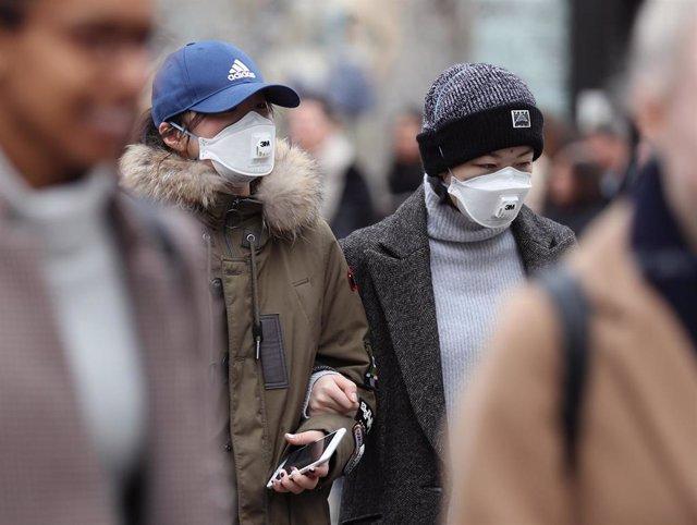 Imagen de varias personas con mascarillas en Londres.