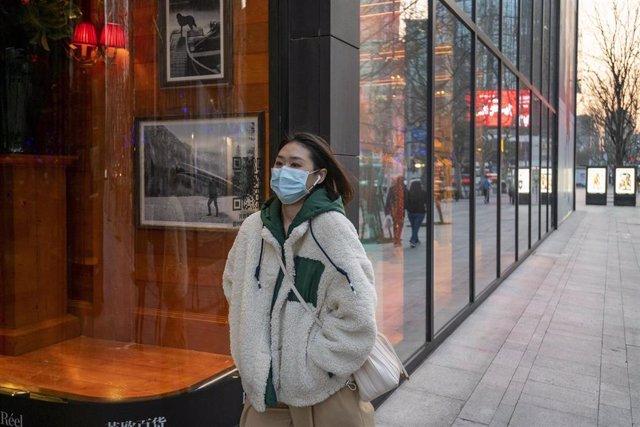 Imagen de una mujer con mascarilla en Shanghái.