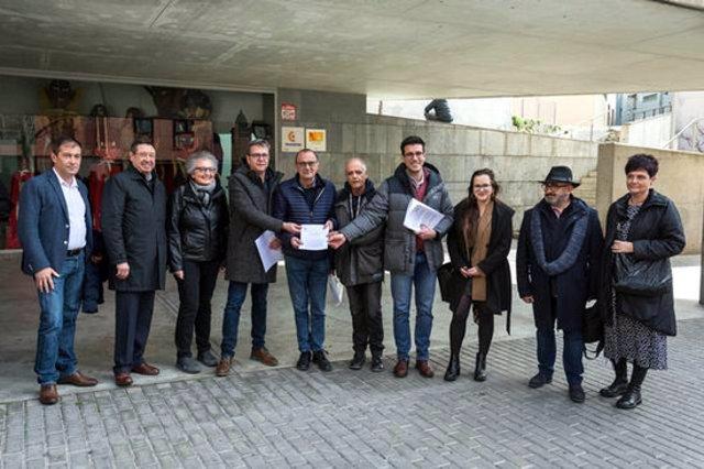 Pla general dels representants de les diferents institucions i entitats amb el manifest que se'ls ha lliurat abans de la reunió, el 7 de març de 2020. (Horitzontal)