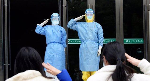 Dos pacientes libres de coronavirus saludan a dos médicos militares en el momento en el que salen del hospital al recibir el alta
