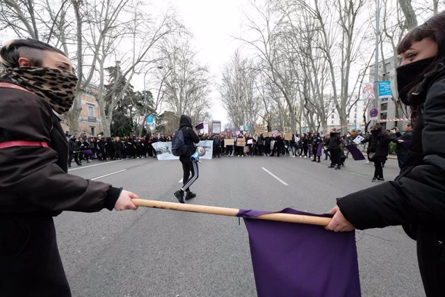 Dos mujeres con la cara tapada que sujetan un palo con una bandera morada ante la manifestación del 8M (Día Internacional de la Mujer), en Madrid a 8 de marzo de 2020.