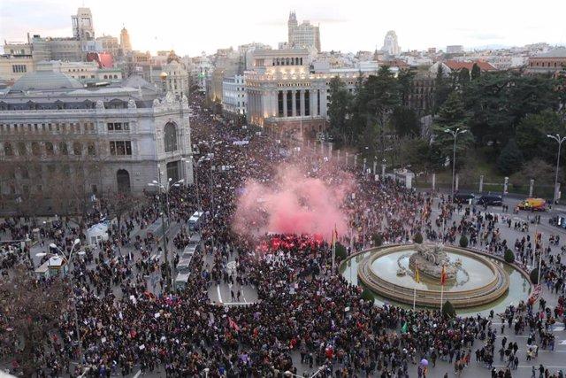 Manifestantes encienden una bengala en la manifestación del 8M (Día Internacional de la Mujer) a su paso por la Plaza de Cibeles, en Madrid a 8 de marzo de 2020.