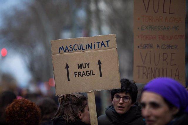 """Una mujer sostiene un cartel en el que pone """"Masculinitat=Muy frágil"""" manifestación del 8M (Día Internacional de la Mujer), en Barcelona a 8 de marzo de 2020."""