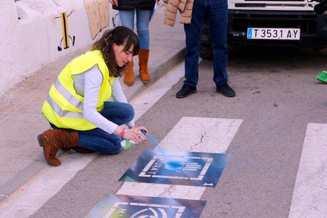 Pla general de la regidora de Qualitat de Vida de Roquetes, Cinta Garcia, pintant els primers pictogrames per ajudar persones amb autisme en un pas de vianants del municipi. Imatge del 10 de març del 2020 (horitzontal)