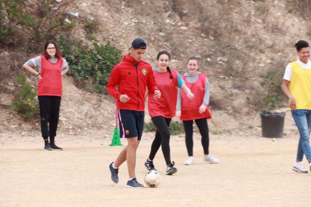 Pla general dels joves que participen en el programa Spectrum - United By Diversity jugant a futbol al pati de l'institut Martí i Franquès de Tarragona. Foto del 10 de març del 2020 (Horitzontal).
