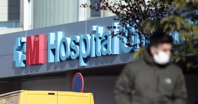 Imagen de recurso de las zonas exteriores del Hospital de Torrejón con una persona que porta mascarilla protectora.