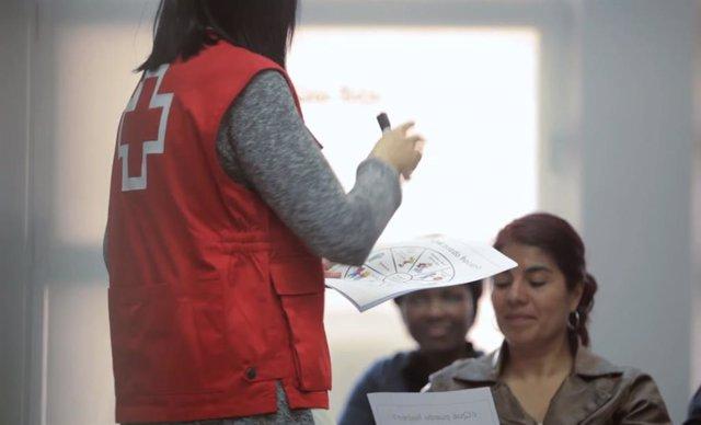 Una voluntària de Creu Roja atén dones usuàries de l'entitat.