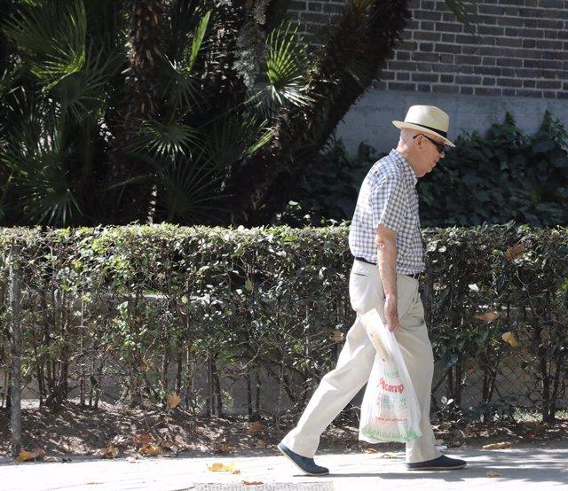 Un hombre de la tercera edad, pasea por una calle de Madrid.