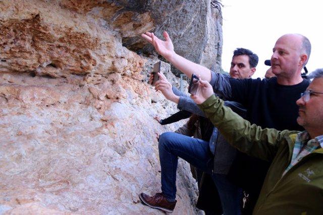 El director del Centre d'Interpretació d'Art Rupestre d'Ulldecona, Agustí Vericat, al centre, explica els detalls de la nova app davant les pintures rupestres de l'Abric I. Imatge del 10 de març de 2020. (horitzontal)