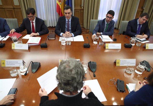 Salvador Illa (1i), habla con Pedro Sánchez (2i), acompañados de Fernando Simón (frente a Sánchez), durante el comité de evaluación y seguimiento del coronavirus en Madrid, (España), a 11 de marzo de 2020.