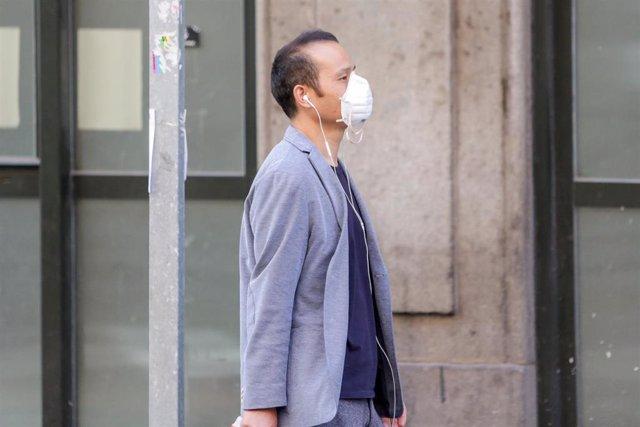 Un transeúnte utiliza una mascarilla para caminar en pleno brote de coronavirus en Madrid (España), a 10 de marzo de 2020.