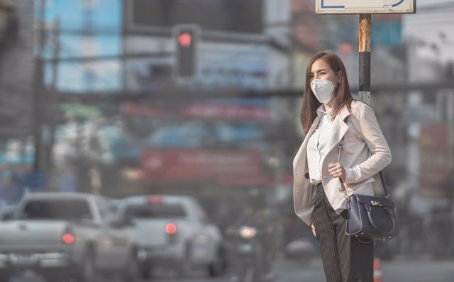 Contaminación, mujer con mascarilla.