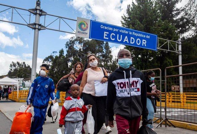 Los miembros de una familia, ataviados todos ellos con mascarillas, cruzan la frontera de Colombia con Ecuador.