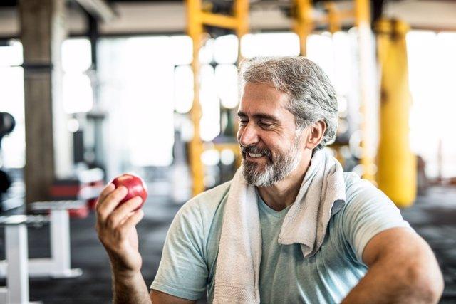Hombre maduro comiendo fruta.