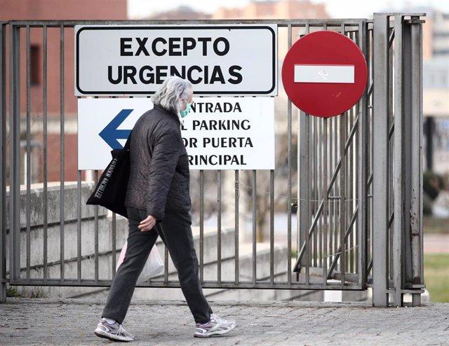 Una mujer protegida con mascarilla ante el avance del coronavirus pasea cerca de la puerta de Urgencias del Hospital Universitario Fundación Alcorcón, en Alcorcón / Madrid (España), a 12 de marzo de 2020.