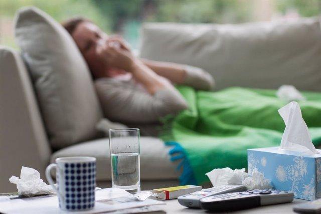 Mujer enferma con gripe. Resfriado, tos, mocos, pañuelos de papel.