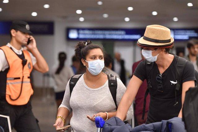 Personas con mascarillas en el aeropuerto de Buenos Aires.