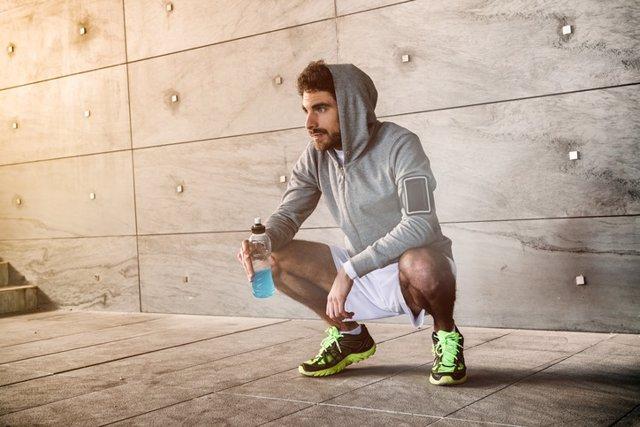 Hombre de cuclillas tras hacer deporte. Bebida isotónica.