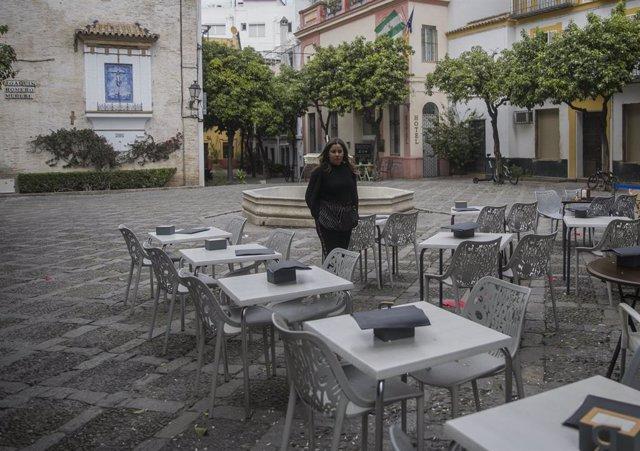Imágenes del impacto del virus del Coronavirus en el sector turístico . Una camarera espera la llegada de clientes en un restaurante del barrio de Santa Cruz, en Sevilla (Andalucía, España), a 03 de marzo de 2020.