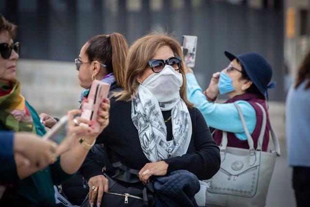 Una mujer camina por zonas cercanas a la Sagrada Familia protegida con un pañuelo en la boca ante el avance del coronavirus en Barcelona, ciudad donde aún no se aprecia de la misma manera que en la capital el impacto que el virus está teniendo en el turis