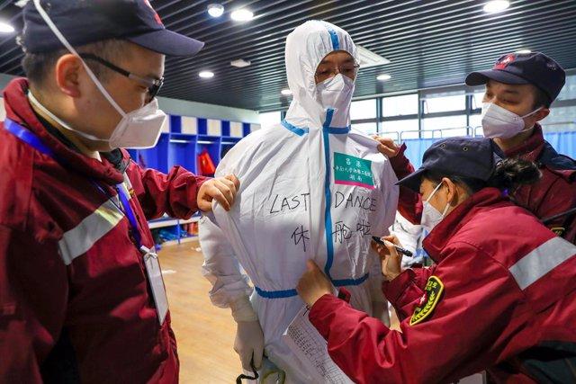 """Treballadors mèdics a Wuhan escriuen el missatge """"últim ball"""" en el vestit de la seva companya després de confirmar el tancament dels 16 hospitals temporals oberts pel brot del coronavirus."""