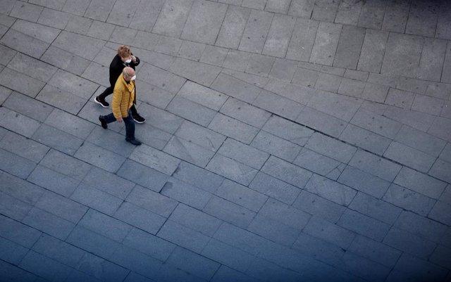 Dos personas caminan por el centro de Madrid protegidos con mascarilla para evitar el contagio de coronavirus, en Madrid (España), a 13 de marzo de 2020.
