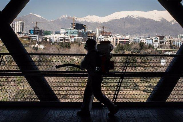 Un treballador sanitari desinfecta un pont a l'Iran.