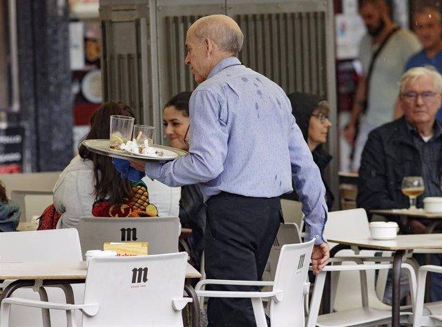 Un cambrer a la terrassa d'un bar de Madrid.