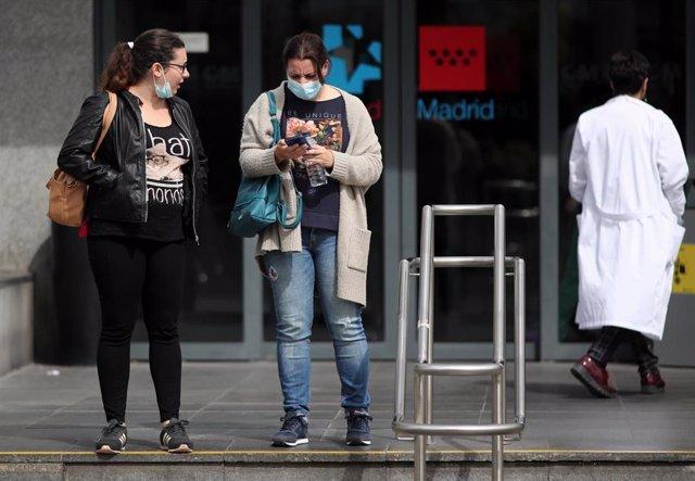 """Dos mujeres protegidas con mascarilla a las afueras del Hospital de la Paz donde se ha habilitado un espacio para atender """"en mejores condiciones"""" a pacientes sospechosos de coronavirus, en Madrid (España), a 12 de marzo de 2020."""