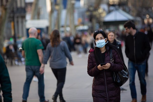 Una mujer con mascarilla camina por las Ramblas de Barcelona.