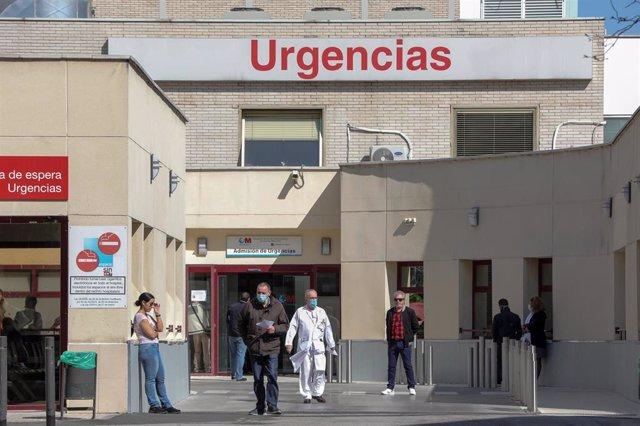 Varias personas protegidas con mascarilla se encuentran cerca de la puerta de Urgencias del Hospital Gregorio Marañón, un día después de que el presidente del Gobierno, Pedro Sánchez, declarase el Estado de Alarma debido a la crisis del coronavirus en Esp