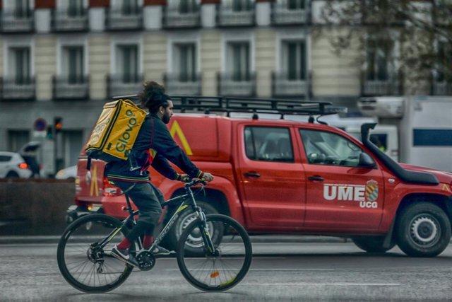 Un repartidor en bici circula por una calle de Madrid al lado de un vehículo de la UME el 15 de marzo de 2020.