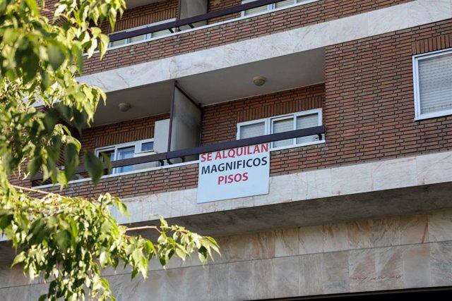 En el balcón de un piso, se ve colgado un cartel en el que se lee 'Se alquilan magníficos pisos'.