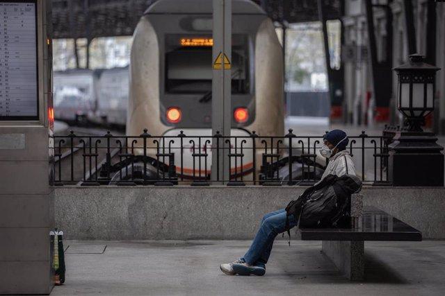Un home protegit amb una mascarilla espera assegut en un banc en una estació de tren de Barcelona durant el segon dia laborable de l'estat d'alarma pel coronavirus, a Barcelona (Espanya), a 17 de març de 2020. (arxiu)
